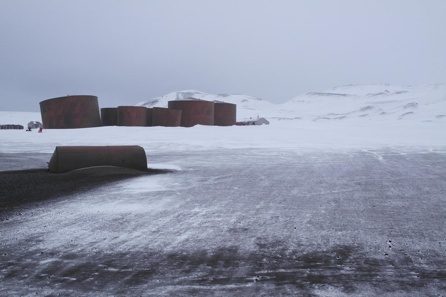 Drifting snow on the desolate beach of Whalers Bay, with the ruins of old fuel tanks