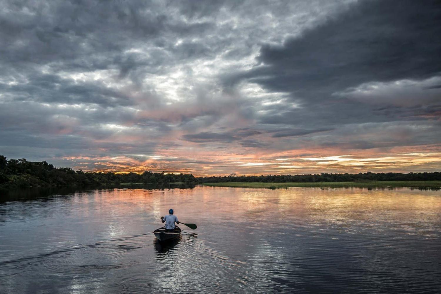 Man sailing the Amazon river at dusk