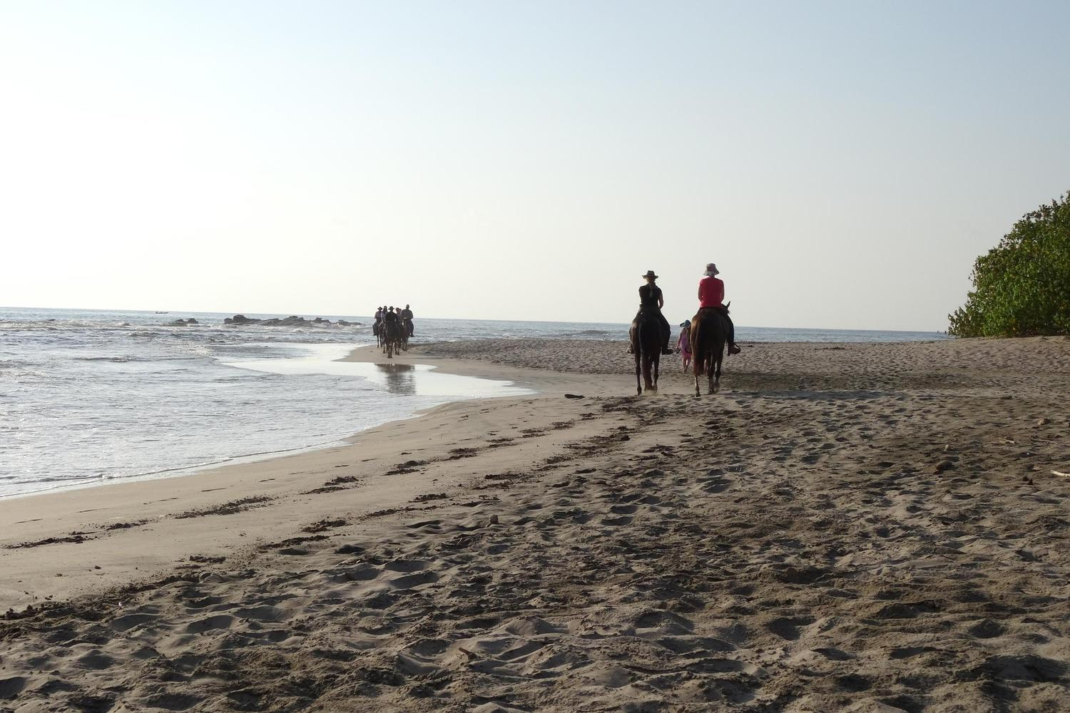Riding horses along San Juanillo beach on the Pacific coast of Costa Rica