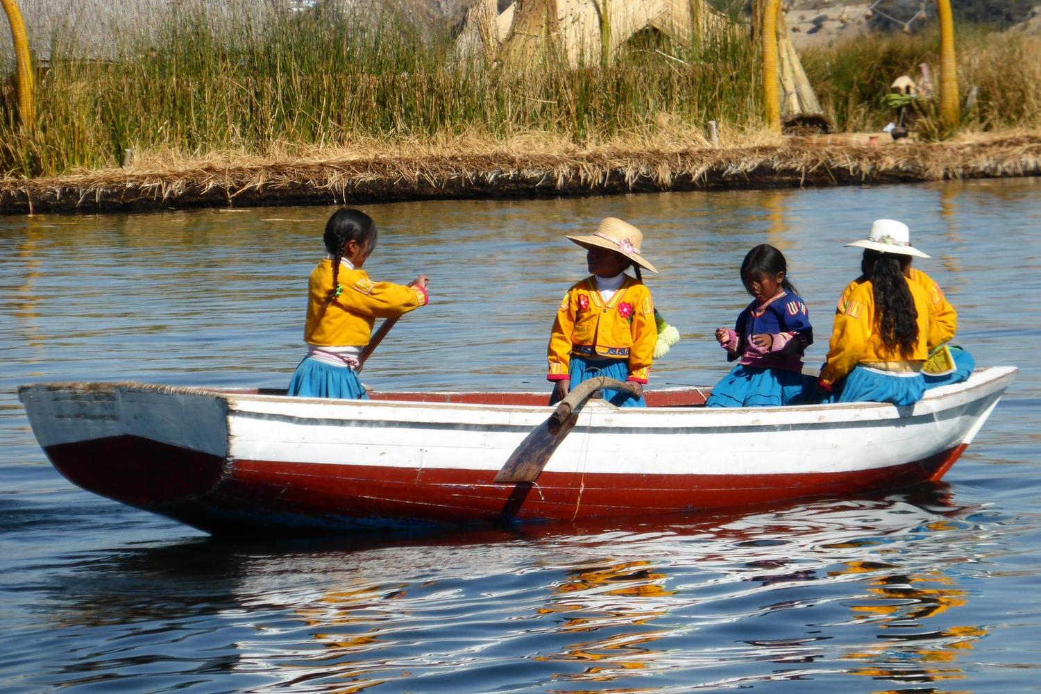 Girls rowing between reed islands in Lake Titicaca